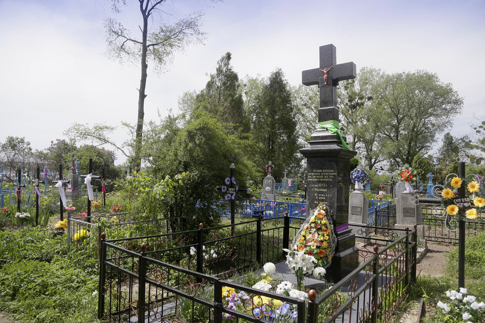 "Photo - In this picture taken May 10, 2013, a monument pays tribute to civilians who were burned alive during WWII in Pidhaitsi close to Ukraine's western city of Lutsk. The monument reads: ""To our parents, wives, children, who were murdered by the German occupants on December 3, 1943 in Pidhaitsi. 21 people, including 9 children."" Evidence uncovered by AP indicates that Ukrainian Self Defense Legion commander Michael Karkoc's unit was in the area at the time of the massacre. (AP Photo/Efrem Lukatsky)"