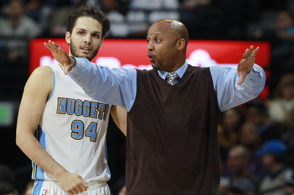 Photo - Denver Nuggets head coach Brian Shaw, right, confers with guard Evan Fournier, of France, during a time out against the Golden State Warriors in the third quarter of the Warriors' 116-112 victory in an NBA basketball game in Denver on Wednesday, April 16, 2014. (AP Photo/David Zalubowski)