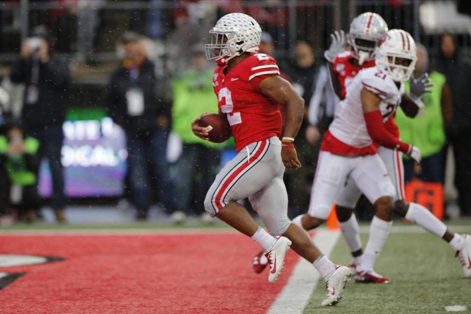 Photo - Ohio State running back J.K. Dobbins, left, scores a touchdown against Wisconsin during the second half of an NCAA college football game Saturday, Oct. 26, 2019, in Columbus, Ohio. Ohio State beat Wisconsin 38-7. (AP Photo/Jay LaPrete)