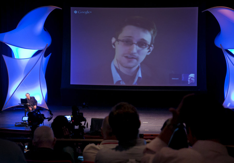 Photo - FILE - In this June 5, 2014 file photo, former NSA contractor Edward Snowden participates in a conversation via video with John Perry Barlow, co-founder & vice chairman of the Electronic Frontier Foundation, at the 2014 Personal Democracy Forum, at New York University in New York. The boundary between the online and physical worlds got blurry last week when Sony's PlayStation Network was disabled by an online attack, while an American Airlines passenger jet carrying a Sony executive was diverted due to a bomb threat on Twitter. Snowden told Wired magazine early August that the NSA had secretly planned a cyberwarfare program, codenamed MonsterMind, that could automatically fire back at cyberattacks from foreign countries without any human involvement. (AP Photo/Richard Drew, File)