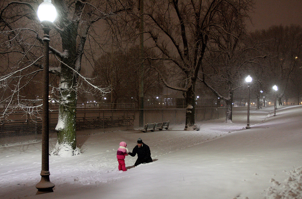 Photo - A father plays with his son on Boston Common in Boston, during a snow storm Friday evening, Feb. 8, 2013. Snow began to fall as a massive blizzard headed for the American Northeas, sending residents scurrying to stock up on food and supplies ahead of a storm poised to dump up to 3 feet of snow from New York City to Boston and beyond. (AP Photo/Palm Beach Post, Mark Edelson)  MAGS OUT; TV OUT; NO SALES