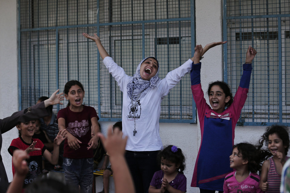Photo - Volunteer Nisreen Shawa, 25, centre, leads a play session with displaced Palestinian children at a U.N. school where they had sought refuge along with their families during the war, in Gaza City, Gaza Strip, Thursday, Aug. 7, 2014. Taking advantage of the continuing ceasefire, volunteers from the local non-profit NGO 'Tomooh' (Ambition), arranged a special play session for children to try and lessen the stress they've been enduring after the weeks of conflict. In the playground the children got a chance to sing and play group games under the caring eye of volunteers. 'We want to bring back hope to their hearts', Shawa said. (AP Photo/Lefteris Pitarakis)