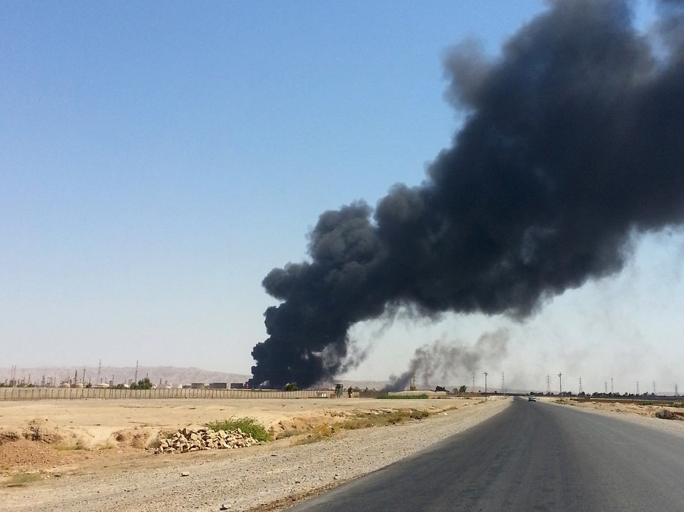Photo - A column of smoke rises from an oil refinery in Beiji, some 250 kilometers (155 miles) north of Baghdad, Iraq, Thursday, June 19, 2014. The fighting at Beiji comes as Iraq has asked the U.S. for airstrikes targeting the militants from the Islamic State of Iraq and the Levant. While U.S. President Barack Obama has not fully ruled out the possibility of launching airstrikes, such action is not imminent in part because intelligence agencies have been unable to identify clear targets on the ground, officials said. (AP Photo)