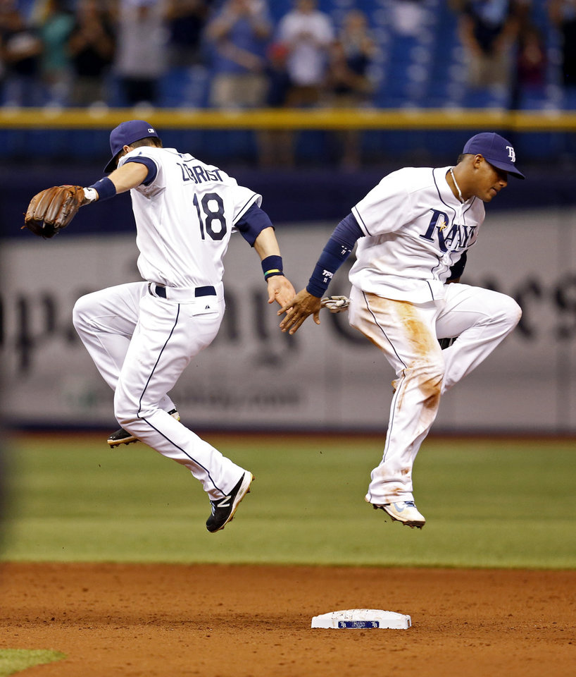 Photo - Tampa Bay Rays' Ben Zobrist, left, and Yunel Escobar celebrate the team's 8-1 win over the Texas Rangers in a baseball game Friday, April 4, 2014, in St. Petersburg, Fla. (AP Photo/Mike Carlson)