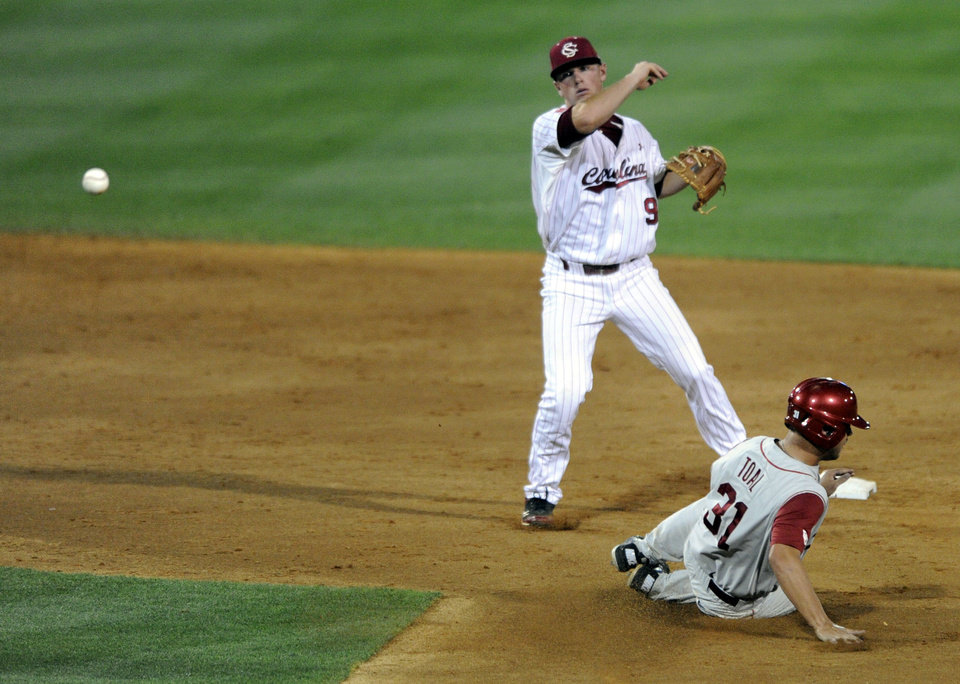 Photo - South Carolina's Joey Pankake (9) turns a double play as Oklahoma's Tanner Toal (31) slides underneath in the third inning of an NCAA college super regional baseball tournament game in Columbia, S.C., Saturday, June 9, 2012. (AP Photo/Mary Ann Chastain) ORG XMIT: SCMC109