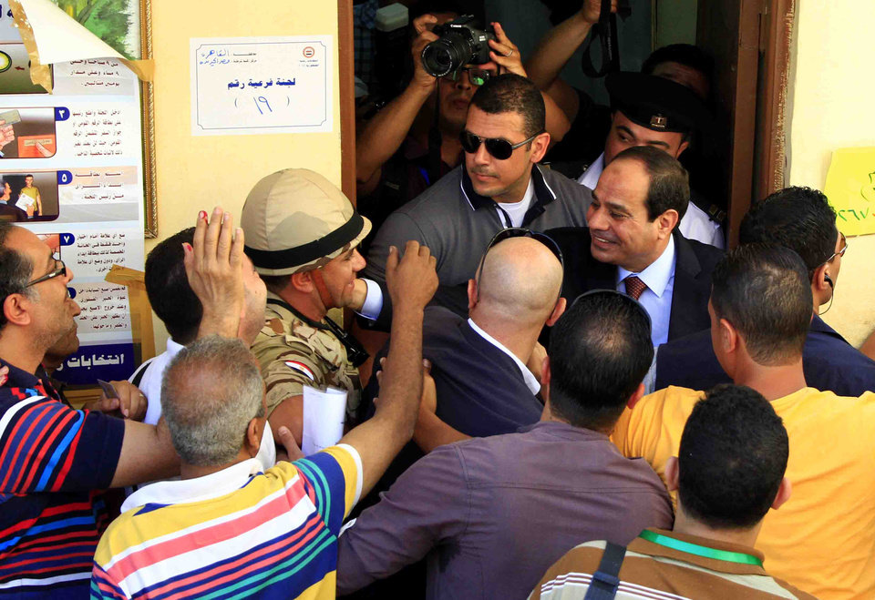 Photo - Presidential hopeful Abdel-Fattah el-Sissi greets voters at a polling site on the first day of voting in Cairo, Egypt, Monday, May 26, 2014.  Egyptians are choosing a new president on Monday in an election that comes nearly a year after the military's ouster of the nation's first freely elected president, the Islamist Mohammed Morsi. The man who removed Morsi, retired military chief Field Marshal Abdel-Fattah el-Sissi, is practically assured of a victory in the vote, which is being held over two days, Monday and Tuesday.(AP Photo/Lobna Tarek, El Shorouk Newspaper) EGYPT OUT