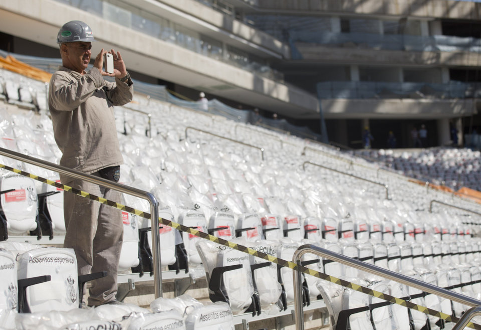 Photo - A worker takes a picture at the Itaquerao, the stadium that will host the World Cup opener in less than three months in Sao Paulo, Brazil, Saturday, March 15, 2014. The Itaquerao was one of the six stadiums that were supposed to be finished by the end of 2013, but a crane collapse that killed two workers in November caused significant delays to the venue where Brazil will play Croatia on June 12. The stadium is not expected to be ready before mid-April. (AP Photo/Andre Penner)