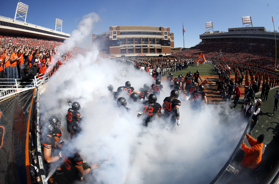 Photo - Oklahoma State runs on to the field during a college football game between Oklahoma State University (OSU) and Texas Christian University (TCU) at Boone Pickens Stadium in Stillwater, Okla., Saturday, Oct. 27, 2012. Photo by Sarah Phipps, The Oklahoman