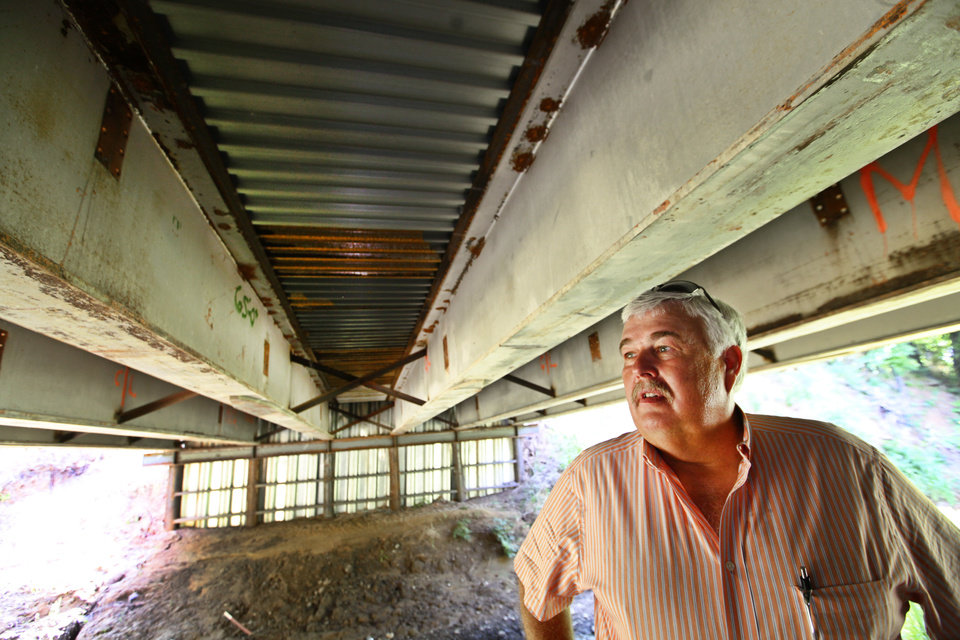 McClain County District 2 Commissioner Wilson Lyles stands beneath a bridge near Washington, OK, that was built using beams from the old Interstate 40 Crosstown Expressway. Photo BY  DAVID MCDANIEL,  THE OKLAHOMAN