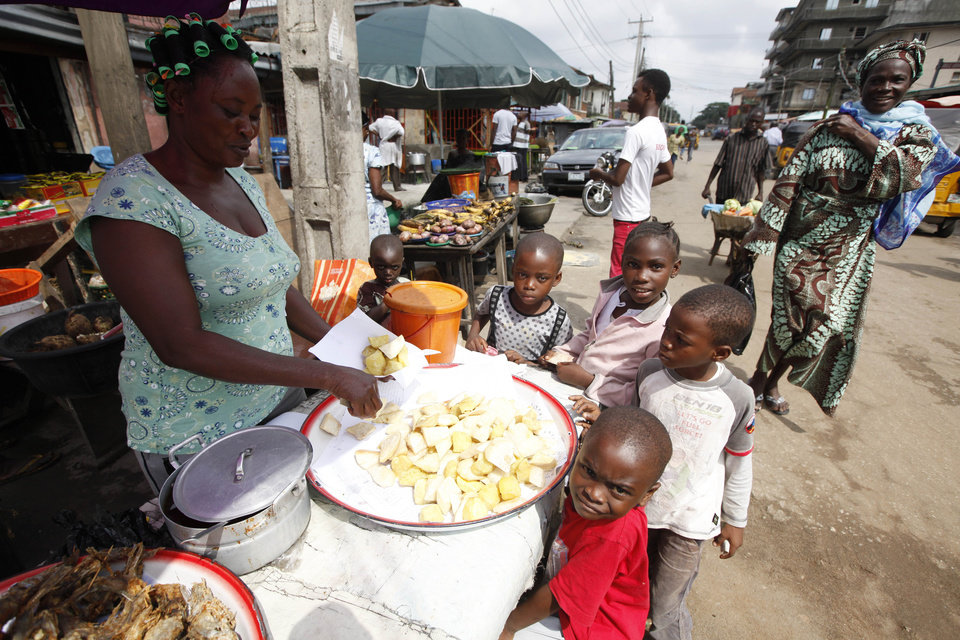 Photo - Children buy fried potatoes on a street in Lagos, Nigeria, Thursday Aug. 7, 2014. West Africans battling to contain the spread of Ebola will have to wait for months until a potentially life-saving experimental drug used on two Americans infected with the dreaded disease could even be made, officials said. There's little of the experimental drug ZMapp available now, and even if it can be made in large quantities, its safety and effectiveness haven't been tested yet. (AP Photo/Sunday Alamba)
