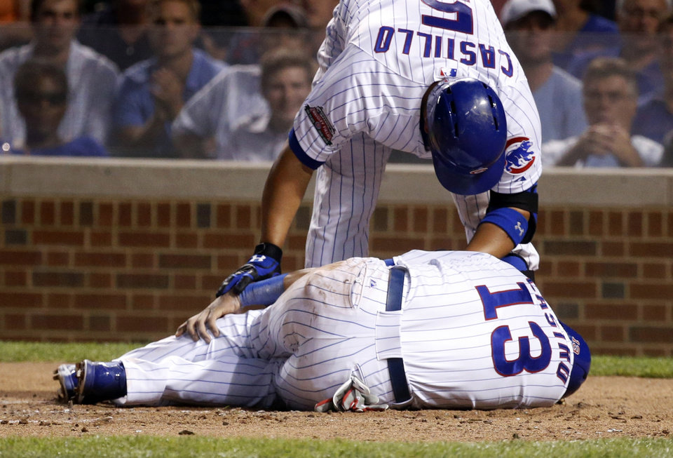 Photo - Chicago Cubs' Welington Castillo looks over Starlin Castro, bottom, after Castro injured himself after sliding safely into home plate, scoring on a single by Jorge Soler, during the first inning of a baseball game against the Milwaukee Brewers, Tuesday, Sept. 2, 2014, in Chicago. (AP Photo/Charles Rex Arbogast)