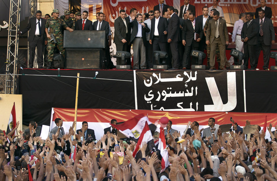 Photo -   FILE - In this Friday, June 29, 2012 file photo, new Egyptian President-elect Mohammed Morsi gives a speech at Tahrir Square in Cairo, Egypt. Standing before tens of thousands of adoring supporters in Tahrir Square, Morsi opened his jacket to show he is not wearing a bullet-proof vest. The message is clear: He has nothing to fear because he sees himself as the legitimate representative of Egypt's uprising. His speeches reveal a populist bent, making generous promises that many are skeptical he can keep. And though he began as an awkward and uninspiring speaker, he appears to be striving to reinvent his decidedly uncharismatic public persona. (AP Photo/Khalil Hamra, File)