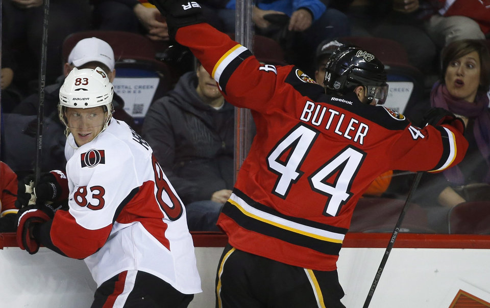 Photo - Ottawa Senators' Ales Hemsky, left, from the Czech Republic, checks Calgary Flames' Chris Butler during the first period of an NHL hockey game Wednesday, March 5, 2014, in Calgary, Alberta. (AP Photo/The Canadian Press, Jeff McIntosh)