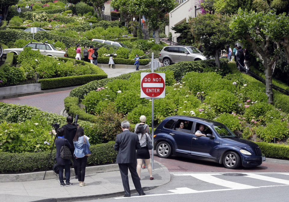 Photo - Motorists and visitors on foot converge on Lombard Street on Tuesday, May 20, 2014, in San Francisco.  San Francisco's crooked street could soon be closed to tourists in the summertime. A transportation commission is scheduled to consider an experimental shutdown of the famously curvaceous block of Lombard Street plus an adjoining block where cars line up and wait.(AP Photo/Marcio Jose Sanchez)