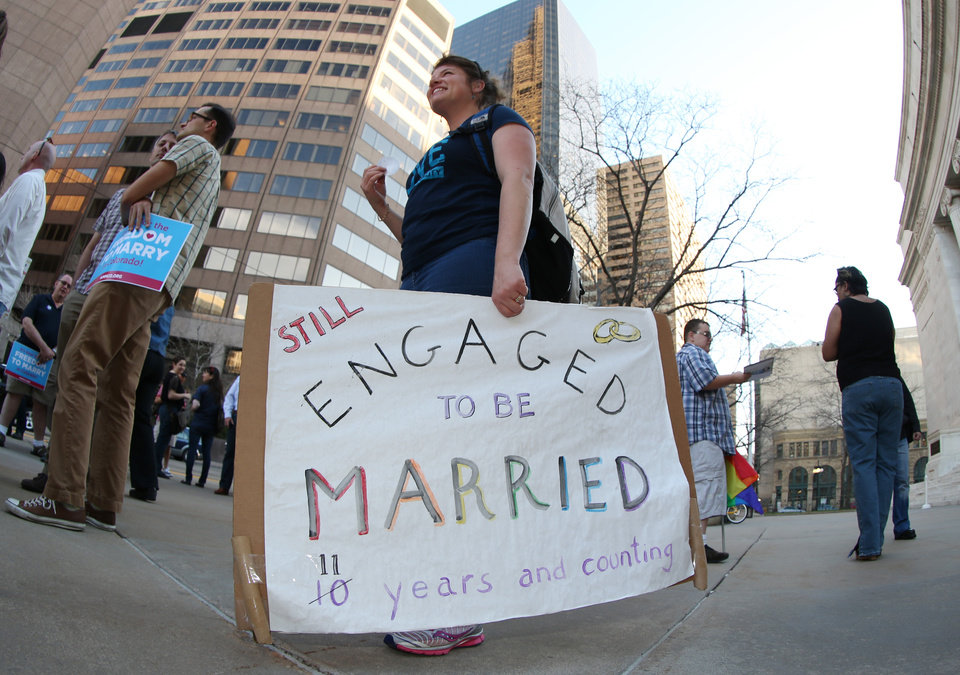 Photo - As viewed through a fisheye lens, Anna Simon of Denver carries a sign about the state of her marriage to her partner at a protest outside the Federal Courthouse in downtown Denver on Wednesday, April 9, 2014. The protest, sponsored by Support Marriage Equality in Colorado, was held as a federal appeals court weighs inside the Denver courthouse whether to give an important victory to gay couples' right to marry in Utah and Oklahoma. (AP Photo/David Zalubowski)