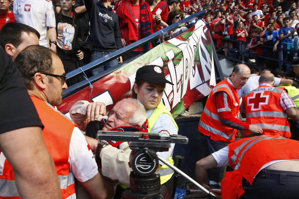 Photo - An Osasuna supporter is helped by assistant after one fence of the stadium was broken while people celebrated a goal of their team, during their last  Spanish League soccer match between Osasuna and Betis,, at El Sadar stadium, in Pamplona northern Spain, Sunday, May 18, 2014. (AP Photo)