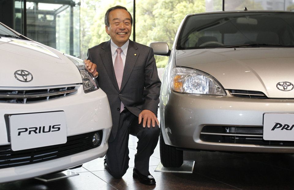 Takeshi Uchiyamada, vice chairman of Toyota Motor Corp., poses for a photo with first, seen at right, and second model of Prius at its headquarters in Tokyo, Wednesday, April 17, 2013. Toyota\'s global sales of gasoline-electric hybrid vehicles have surpassed 5 million in a milestone for a technology that was initially greeted with skepticism. The Japanese automaker, which said Wednesday it had sold 5.125 million hybrid vehicles as of the end of March, started selling the Prius, the world\'s first mass produced hybrid passenger car, in 1997. (AP Photo/Shuji Kajiyama)