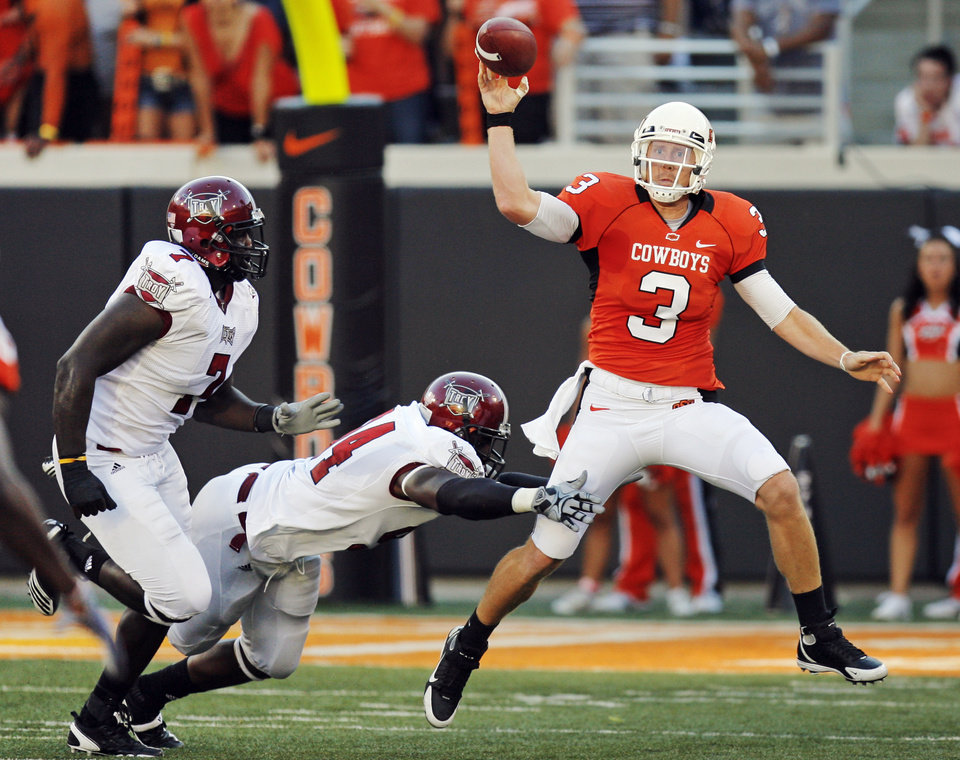 Photo - OSU quarterback Brandon Weeden (3) passes the ball as he is pursued by Troy's Jonathan Massaquoi (94) and Mario Addison (7) in the first quarter during the college football game between the Oklahoma State University Cowboys (OSU) and the Troy University Trojans at Boone Pickens Stadium in Stillwater, Okla., Saturday, Sept. 11, 2010. Photo by Nate Billings, The Oklahoman