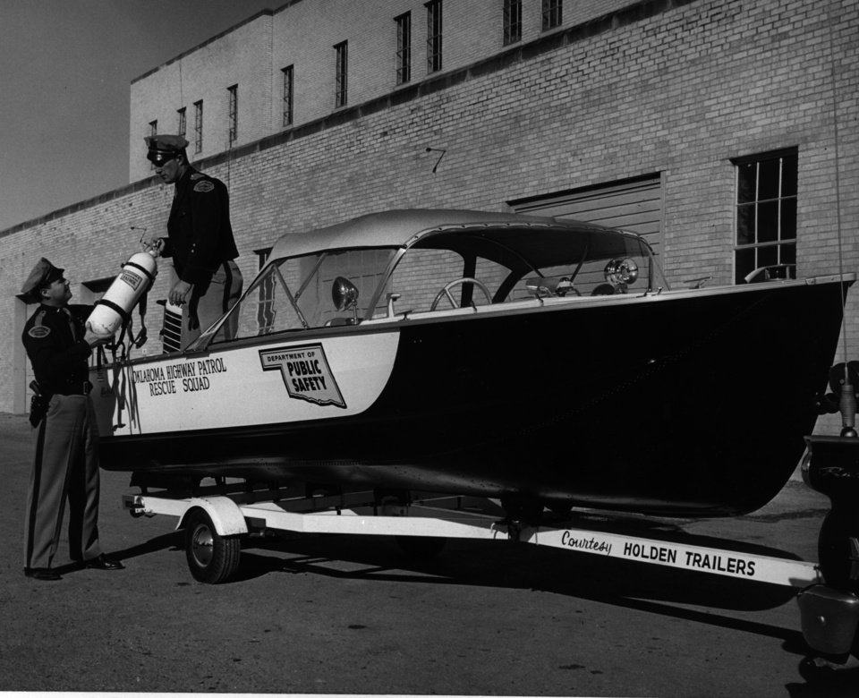 Photo - A new boat presented to the Oklahoman Highway Patrol rescue squad is outfitted by Lts. Sid Berry  and R.E. Frusher in 1960. In addition to state roads and highways, the patrol is responsible for law enforcement on state waterways.  DICK COBB - DICK COBB