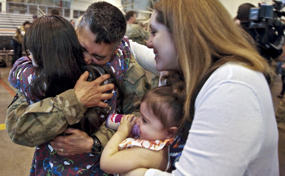 Staff Sgt. Orlando Ornelas is greeted by his daughters Mariah, left, Madelyn and wife Camille during the return ceremony for the National Guard's 45th Infantry Brigade Combat Team troops at the National Guard Base on Thursday, March 15, 2012, in Oklahoma City, Oklahoma.  Photo by Chris Landsberger, The Oklahoman