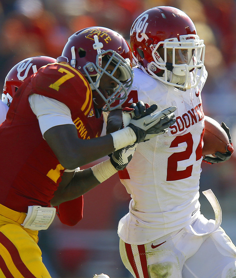 Photo - Oklahoma's Brennan Clay (24) fights off Iowa State's Cliff Stokes (7) during a college football game between the University of Oklahoma (OU) and Iowa State University (ISU) at Jack Trice Stadium in Ames, Iowa, Saturday, Nov. 3, 2012. Oklahoma won 35-20. Photo by Bryan Terry, The Oklahoman