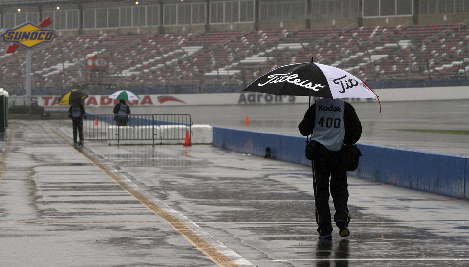Photo - Pit road is virtually empty except for wandering photographers looking for rain features at Talladega Superspeedway in Talladega, Ala., Saturday, May 4, 2013. Rain threatens Saturday's qualifying for Sunday's NASCAR Sprint Cup series Aaron's 499 auto race. (AP Photo/Butch Dill)