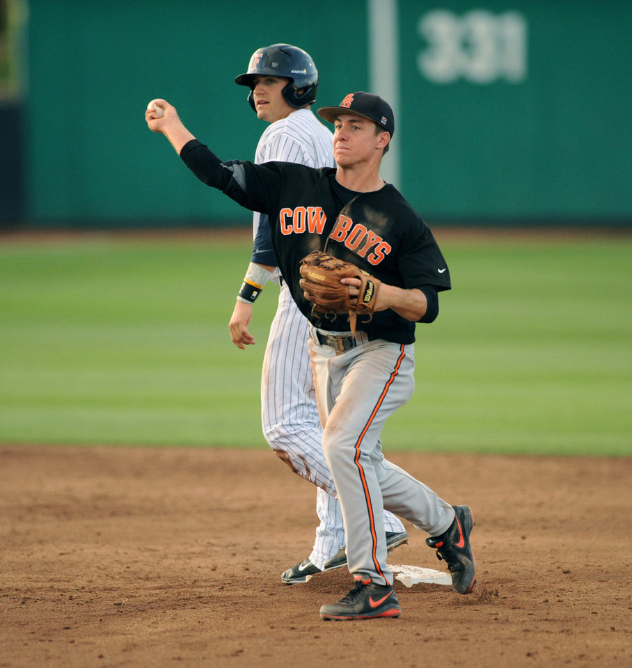 Photo - Fullerton's Clay Williamson, back, watches as  Oklahoma State second baseman Tim Arakawa throws for first base to complete the third out of a triple play in the third inning of an NCAA college baseball regional tournament game in Stillwater, Okla,, Saturday, May 31, 2014. (AP Photo/Brody Schmidt)