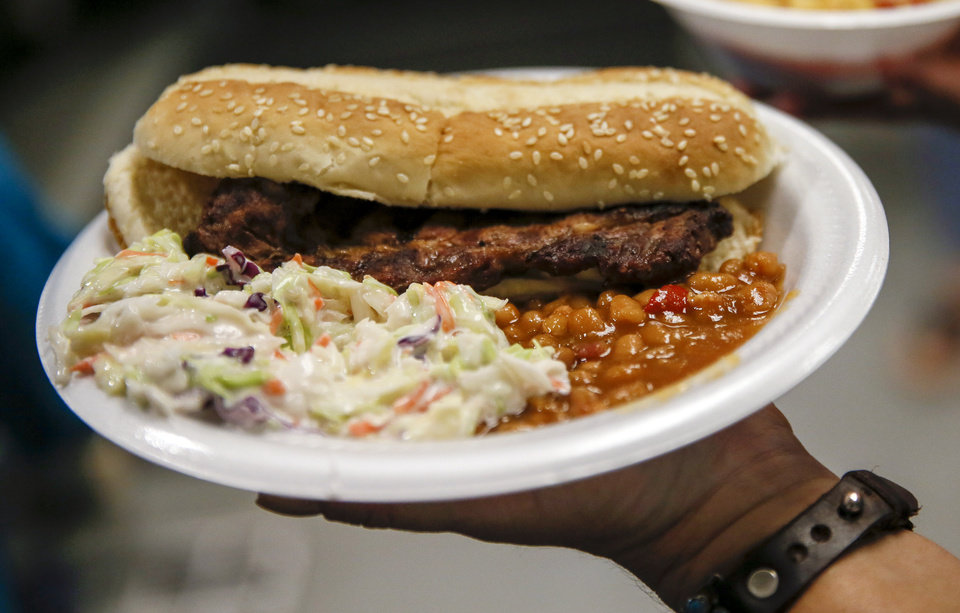 Photo -  Rib-eye steak sandwiches were served with beans and coleslaw at the Homeless Alliance's WestTown day shelter when the Oklahoma Cattlemen's Association and Beef Council served lunch on May 24. [Photo by Nate Billings, The Oklahoman]