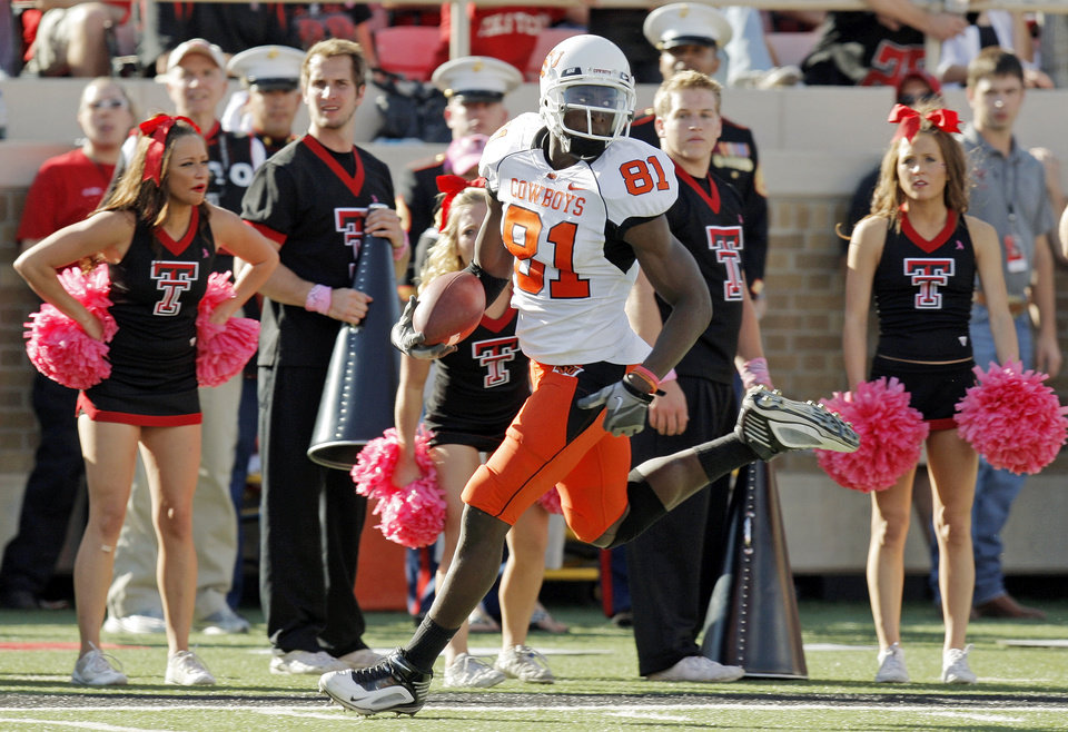 Photo - OSU's Justin Blackmon (81) runs past the Texas Tech cheerleaders on a reception for a touchdown in the third quarter during the college football game between the Oklahoma State University Cowboys and Texas Tech University Red Raiders at Jones AT&T Stadium in Lubbock, Texas, Saturday, October 16, 2010. OSU won, 34-17. Photo by Nate Billings, The Oklahoman
