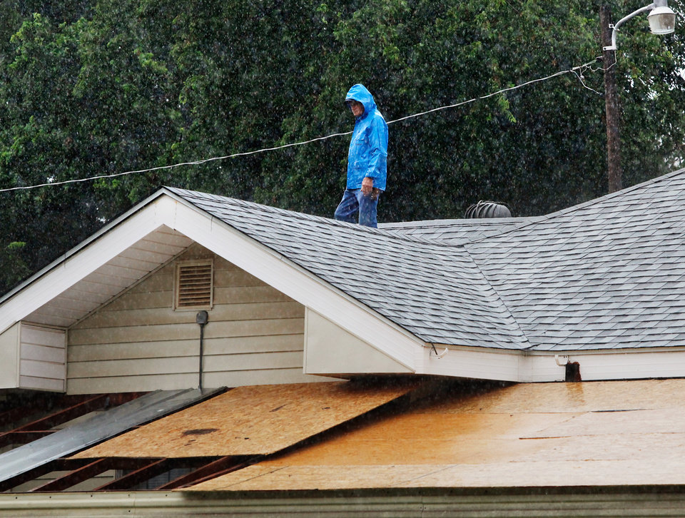 Photo - A man checks the roof of a home for leaks in northwest Oklahoma City. Torrential rain caused flooding in Oklahoma City, Monday, June 14, 2010.     by Jim Beckel, The Oklahoman