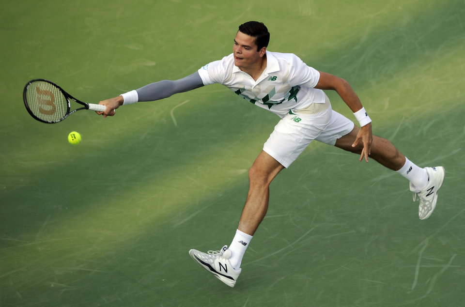 Photo - Milos Raonic, of Canada, lunges for the ball against Jack Sock during a match at the Citi Open tennis tournament, Wednesday, July 30, 2014, in Washington. (AP Photo/Nick Wass)