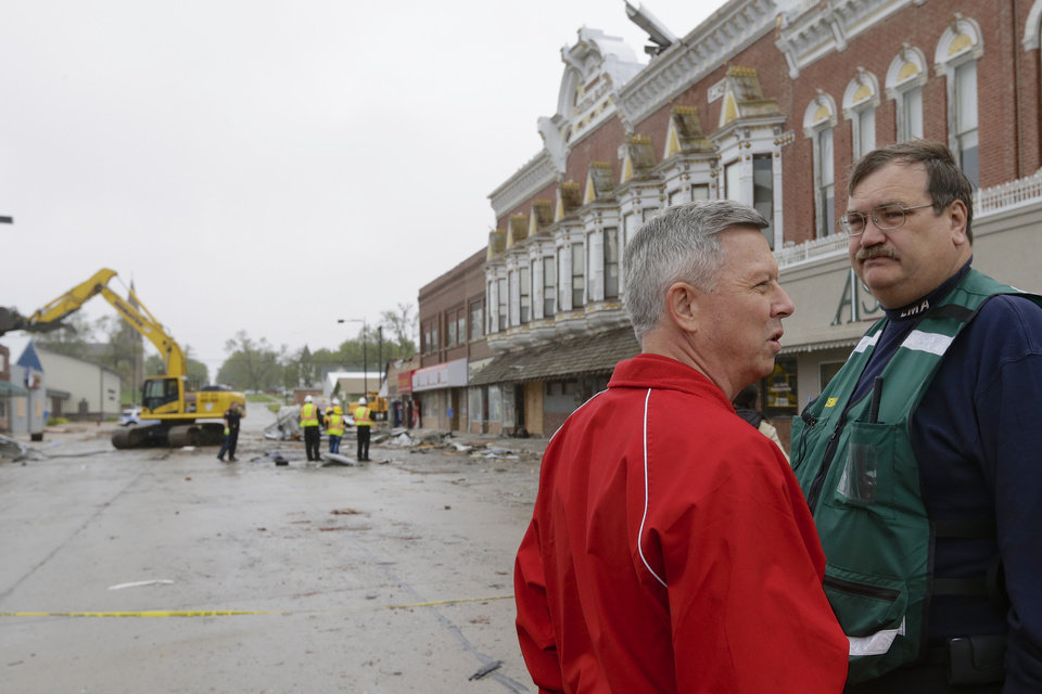 Photo - Nebraska Gov. Dave Heineman, accompanied by Clay County EMA official Loren Uden, right, surveys damage to downtown Sutton, Neb., Monday, May 12, 2014, after a tornado touched down in town on Sunday. Several tornadoes moved across Nebraska on Sunday causing damage to homes and businesses in or near Sutton, Garland, Cordova, Beaver Crossing and Daykin. The storms also left more than 18,000 utility customers without electricity. (AP Photo/Nati Harnik)