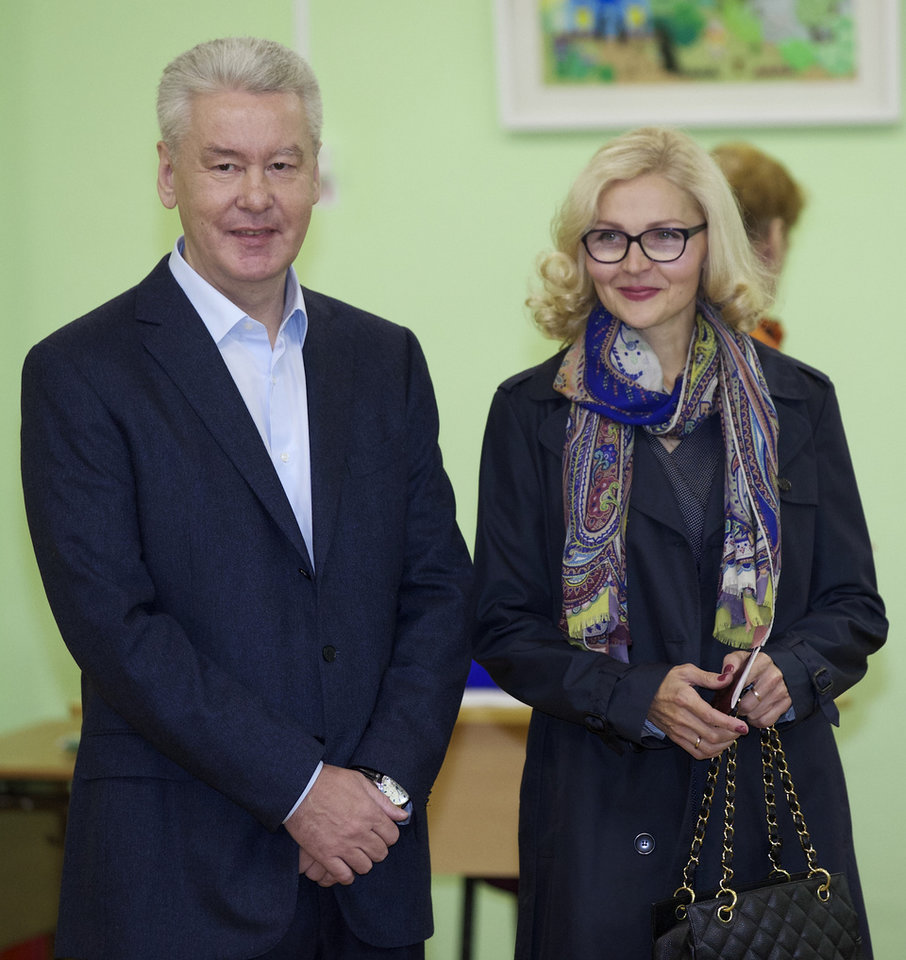Photo - Moscow's acting mayor Sergei Sobyanin, left, and his wife Irina, arrive at a polling station in Moscow, Russia, Sunday, Sept. 8, 2013. Moscow is holding its first mayoral election in a decade. Although an incumbent backed by President Vladimir Putin is expected to win Sunday's election handily, the candidacy of charismatic opposition leader Alexei Navalny is changing Russian politics in ways that could pose a risk for the Kremlin in the months and years ahead. (AP Photo/Alexander Zemlianichenko)
