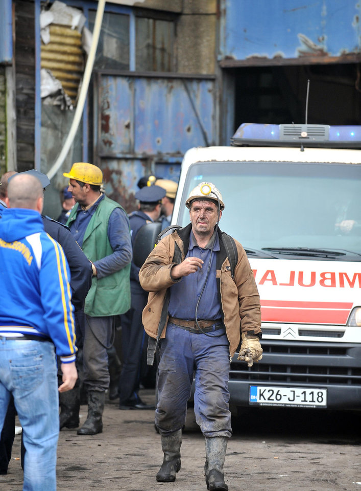 Photo - A rescuer walks away from the Raspotocje coal mine in Zenica, 70 kms north of Sarajevo, Bosnia, Friday, Sept. 5, 2014. Rescuers on Friday were pulling out some of the 34 miners who had been trapped deep inside a coal mine that collapsed in central Bosnia. Tired, their faces smeared with coal dust, the men came out of the Zenica mine one by one, after spending the night more than 500 meters (1,600 feet) below the ground.(AP Photo/Amel Emric)