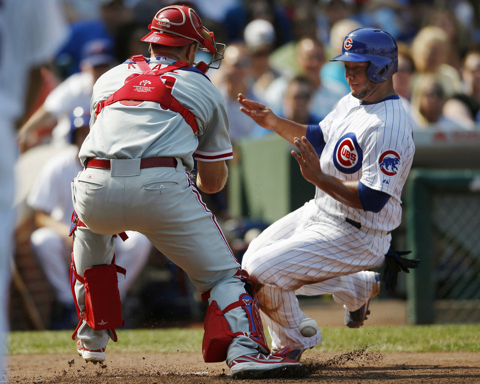 Photo - Chicago Cubs' Welington Castillo safely reaches home as Philadelphia Phillies catcher Erik Kratz looses the ball during the fourth inning of a baseball game on Sunday, Sept. 1, 2013, in Chicago. (AP Photo/Andrew A. Nelles)