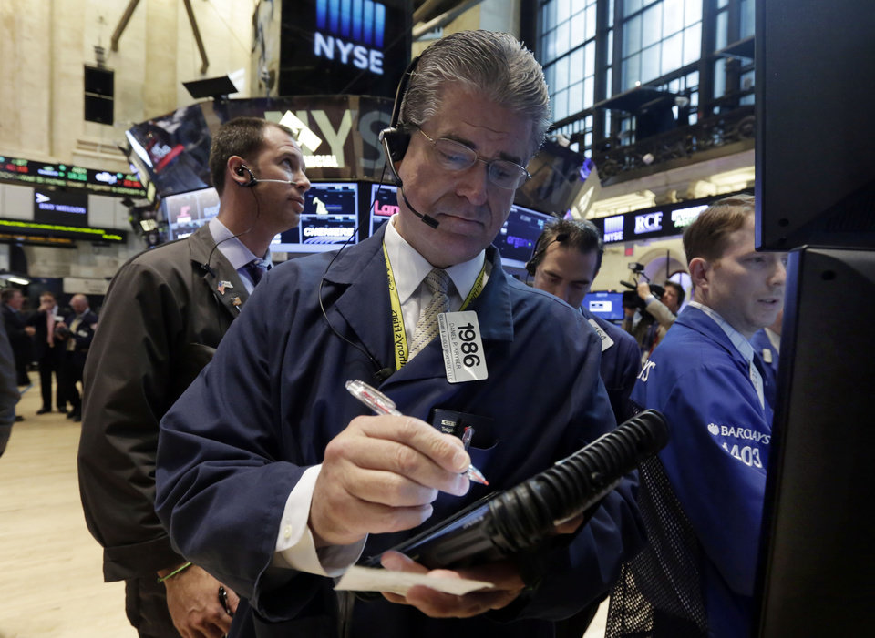 Photo - Trader Daniel Kryger, center, works on the floor of the New York Stock Exchange, Monday, Aug. 4, 2014. U.S. stocks are opening mostly higher as the market recovers from a two-day slide last week. (AP Photo/Richard Drew)