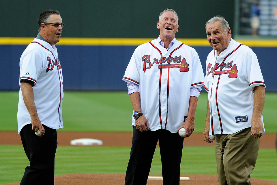 Photo - Hall of Famers Greg Maddux, Tom Glavine and Bobby Cox, left to right, laugh before throwing out the first pitches at a baseball game between the Atlanta Braves and the Washington Nationals, Friday, Aug. 8, 2014, in Atlanta. (AP Photo/David Tulis)