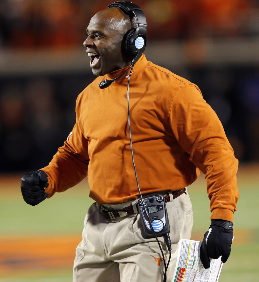 Photo - Texas coach Charlie Strong reacts to a defensive stop by the Longhorns during the college football game between the Oklahoma State University Cowboys (OSU) the University of Texas Longhorns (UT) at Boone Pickens Staduim in Stillwater, Okla. on Saturday, Nov. 15, 2014.  Photo by Chris Landsberger, The Oklahoman