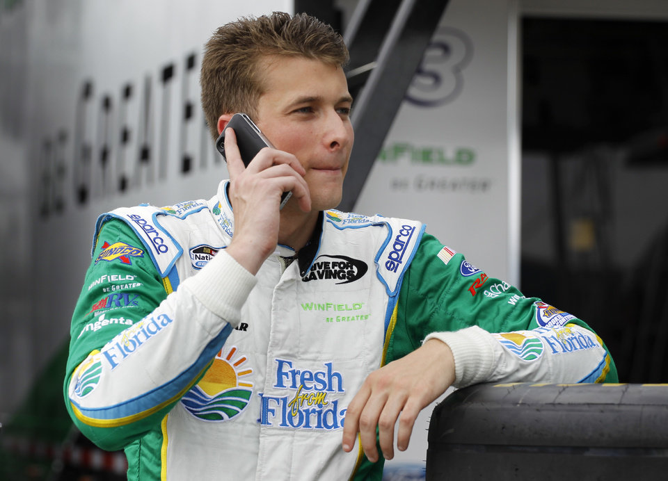 Photo - Dakoda Armstrong talks on a cell phone in the garage area after qualifying for the pole position for the  NASCAR Nationwide series auto race at Daytona International Speedway in Daytona Beach, Fla., Friday, July 4, 2014. (AP Photo/Terry Renna)