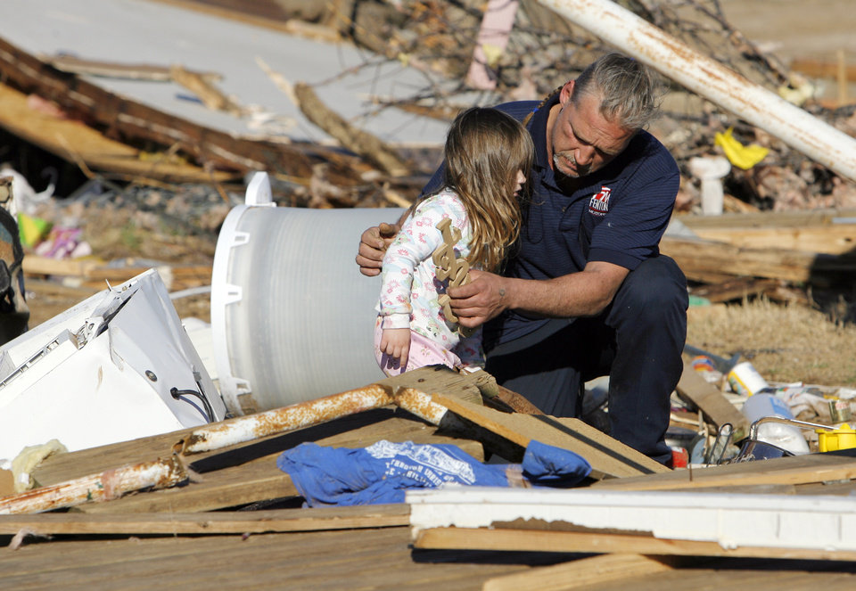 Dennis Parker holds his granddaughter, Brooklyn Hickman, 3, while sifting through belongings from his destroyed mobile home at the Bar K Mobile Home Park in Lone Grove, Okla., Wednesday, February 11, 2009. On Tuesday, February 10, 2009, a tornado moved through Lone Grove killing at least eight people. BY NATE BILLINGS, THE OKLAHOMAN