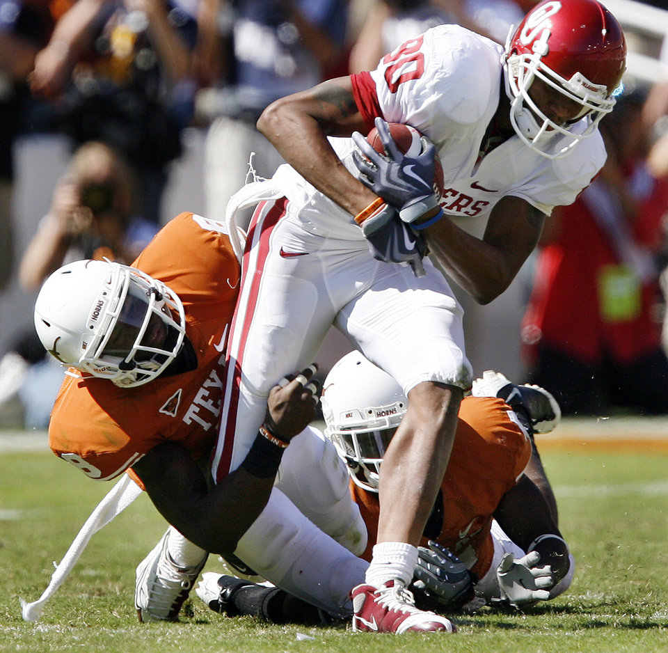 Photo - Oklahoma's Adron Tennell (80) is brought down by Texas' Chykie Brown (8) during the Red River Rivalry college football game between the University of Oklahoma Sooners (OU) and the University of Texas Longhorns (UT) at the Cotton Bowl in Dallas, Texas, Saturday, Oct. 17, 2009. Photo by Chris Landsberger, The Oklahoman