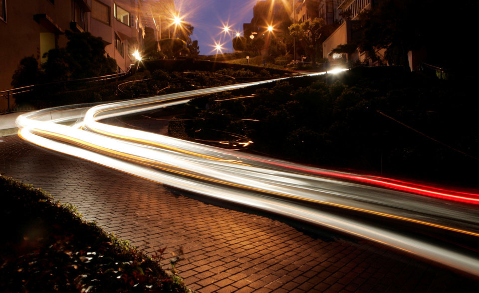 Photo - File - In this April 28, 2008, file photo a long exposure creates streaks of light as motorists wind their way down Lombard Street in San Francisco. San Francisco's crooked street could soon be closed to tourists in the summertime. A transportation commission is scheduled to consider an experimental shutdown of the famously curvaceous block of Lombard Street plus an adjoining block where cars line up and wait.  The move comes in response to complaints from residents about traffic on the street. (AP Photo/Marcio Jose Sanchez, File)