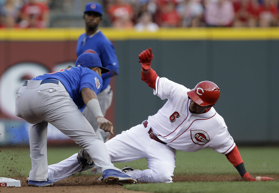 Photo - Cincinnati Reds' Billy Hamilton (6) is tagged out by Chicago Cubs shortstop Starlin Castro trying to steal second base in the third inning of a baseball game, Wednesday, July 9, 2014, in Cincinnati. (AP Photo/Al Behrman)