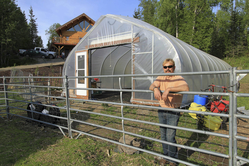Photo - Lee Hecimovich is interviewed about growing artichokes and tomatoes while standing outside of his seasonal high tunnel on Friday, May 23, 2014, in Palmer, Alaska. The USDA's Natural Resource Conservation Service offers financial assistance to growers using the tall hoop houses to extend growing seasons, and has awarded more funding to Alaska for them than any other state. (AP Photo/Dan Joling)