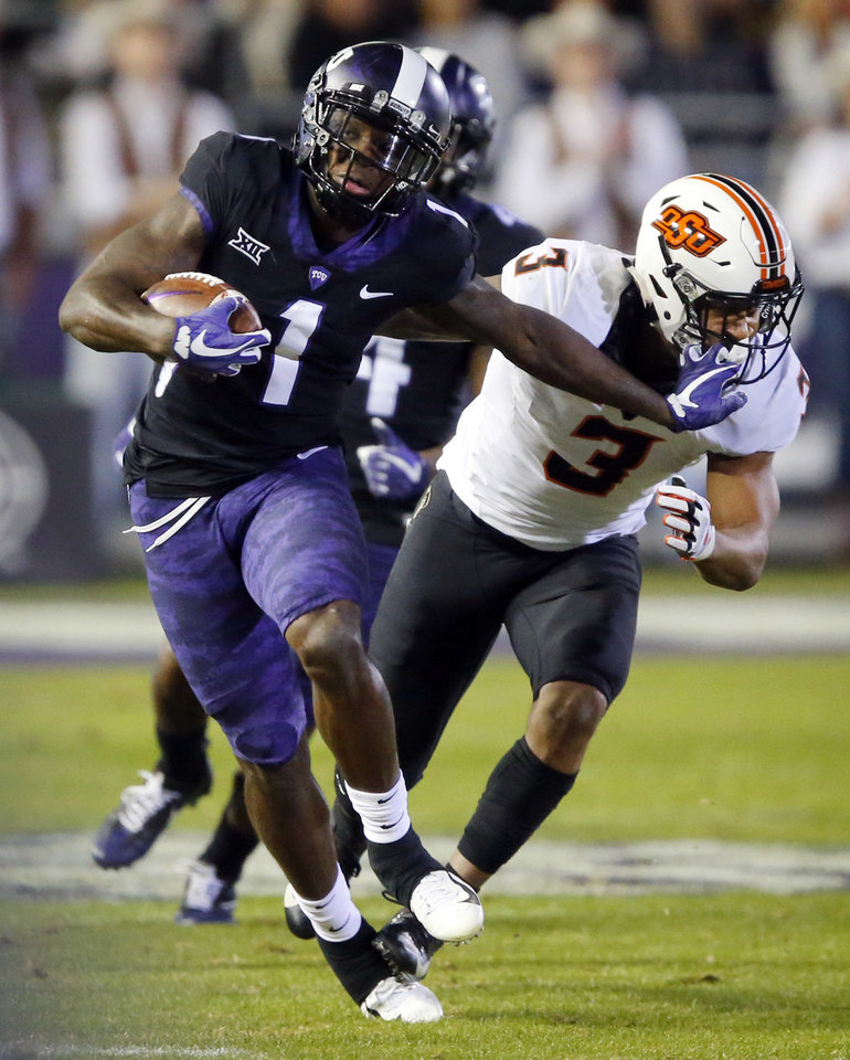 Photo -  TCU wide receiver Jalen Reagor (1) gives Oklahoma State linebacker Kenneth Edison-McGruder (3) a stiff-arm after making a catch during the first quarter Saturday. [AP PHOTO]