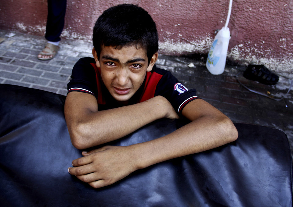 Photo - A Palestinian boy cries after watching his wounded relatives being rushed to emergency rooms at the Nasser hospital following an Israeli air strike in Khan Younis, the southern Gaza Strip, Thursday, July 24, 2014. Israeli troops backed by tanks and aerial drones clashed with Hamas fighters armed with rocket-propelled grenades and assault rifles on the outskirts of Khan Younis, killing many militants, according to a Palestinian health official. Hundreds of people fled their homes as the battle unfolded, flooding into the streets with what few belongings they could carry, many with children in tow. They said they were seeking shelter in nearby U.N. schools. (AP Photo/Hatem Ali)