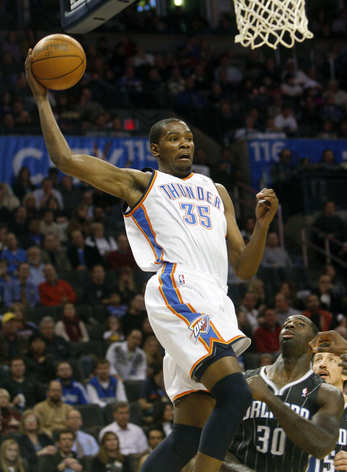 Oklahoma City Thunder forward Kevin Durant, left, goes up for a pass in front of Orlando Magic forward Brandon Bass, right, in the third quarter of an NBA basketball game in Oklahoma City, Thursday, Jan. 13, 2011. Durant had 36 points as Oklahoma City won 125-124.(AP Photo/Sue Ogrocki)