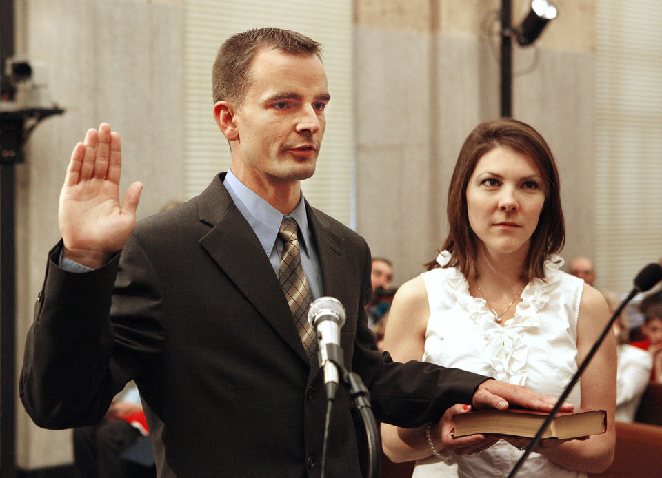 Photo - James Greiner is sworn in Tuesday as Ward 1 city councilman with his wife, Katie Greiner, holding the Bible in Oklahoma City.