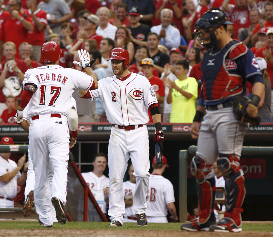 Photo - Cincinnati Reds' Kris Negron (17) is congratulated by Zack Cozart (2) after Negron hit a two run home run off Cleveland Indians starting pitcher Danny Salazar in the fourth inning of a baseball game, Wednesday, Aug. 6, 2014, in Cincinnati. Indians catcher Yan Gomes watches at right. (AP Photo/David Kohl)