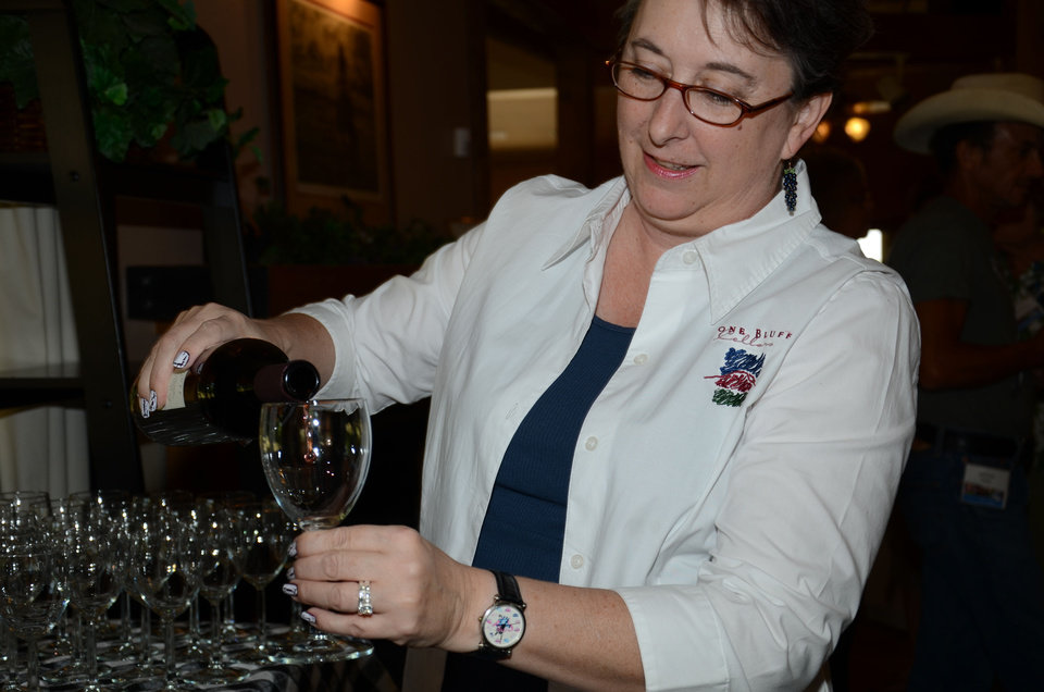 Photo - Dee Selby pours wine for a bus tour participant to sample June 28 at Stone Bluff Cellars in Haskell. Selby is hospitality coordinator of the winery and vineyard. Melissa Pearson, Oklahoma Department of Agriculture, Food & Forestry